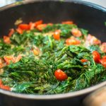 frischen Spinat in der Pfanne mit Zwiebel und Knoblauch zerfallen lassen